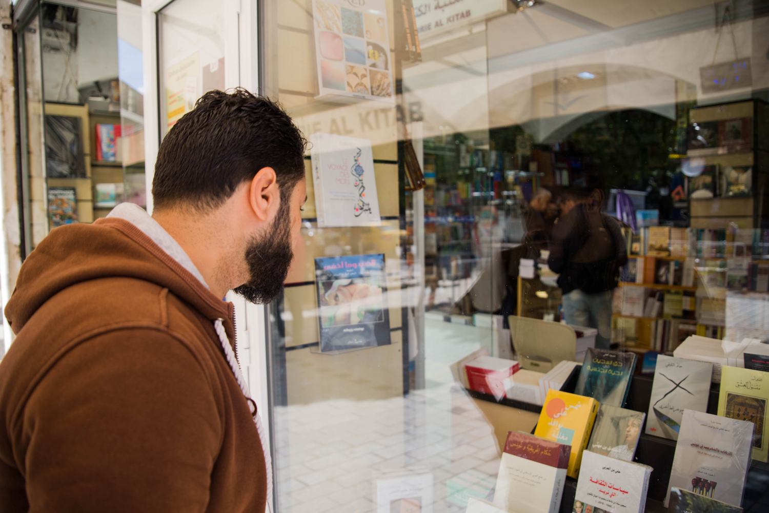 Hosam Athani looks at a copy of Sun on Closed Windows in a bookstore in Tunis.
