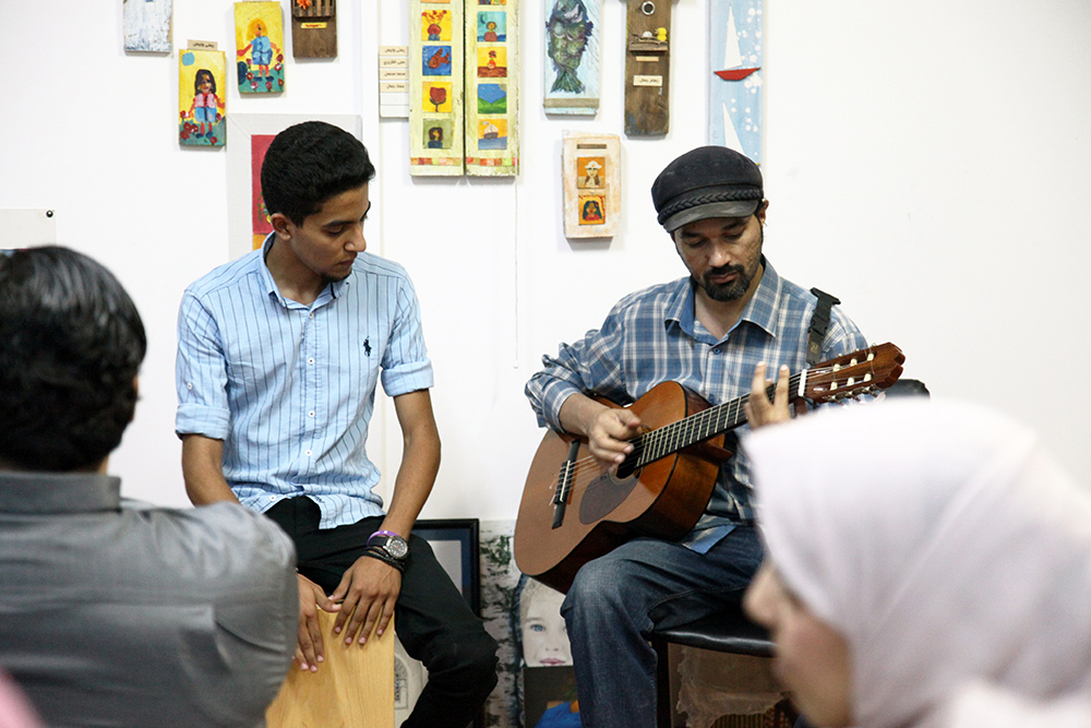 Wadeeh Elatrach playing the guitar while Faraj Al-Selieni plays the cajon.