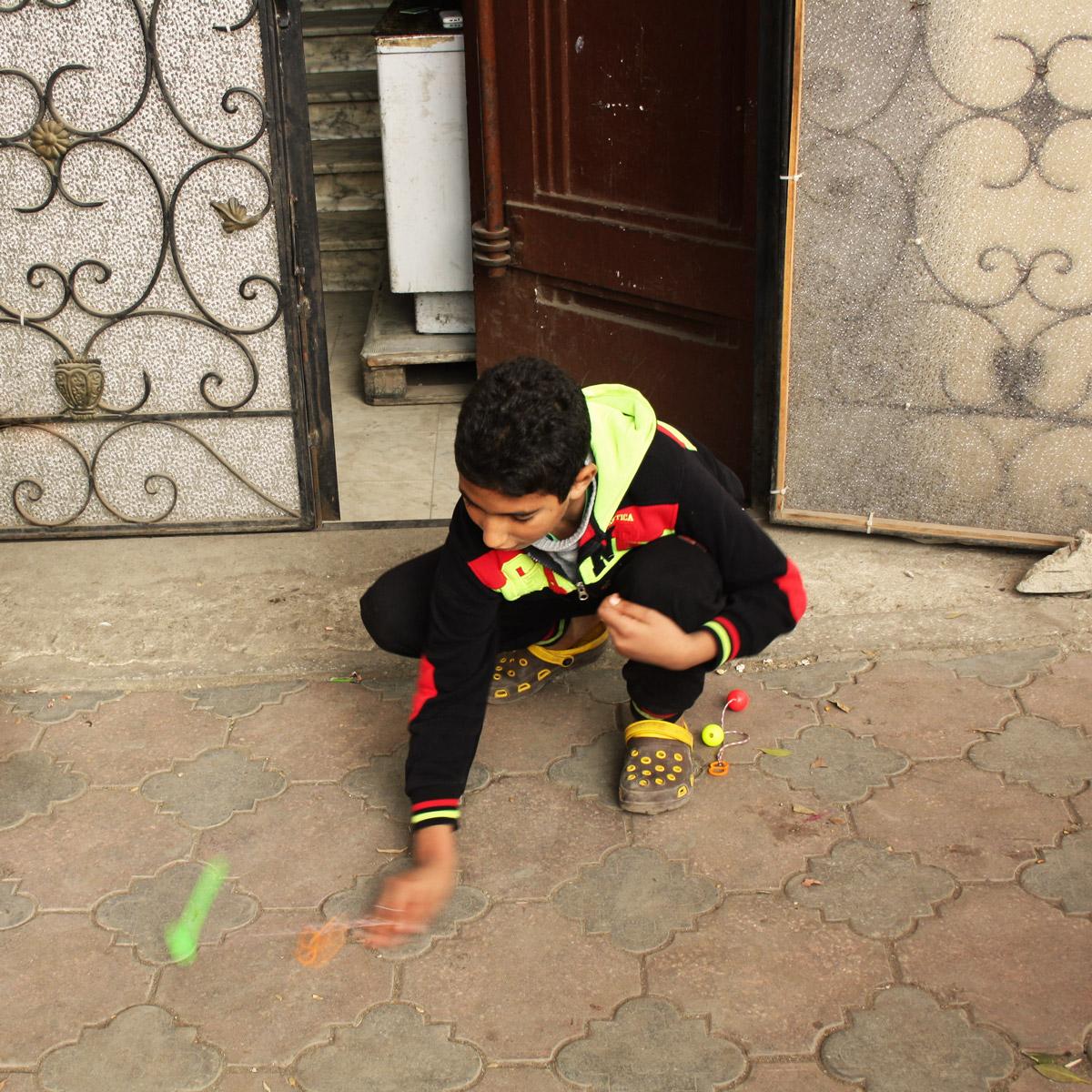 A boy smashing the plastic balls on the concrete.