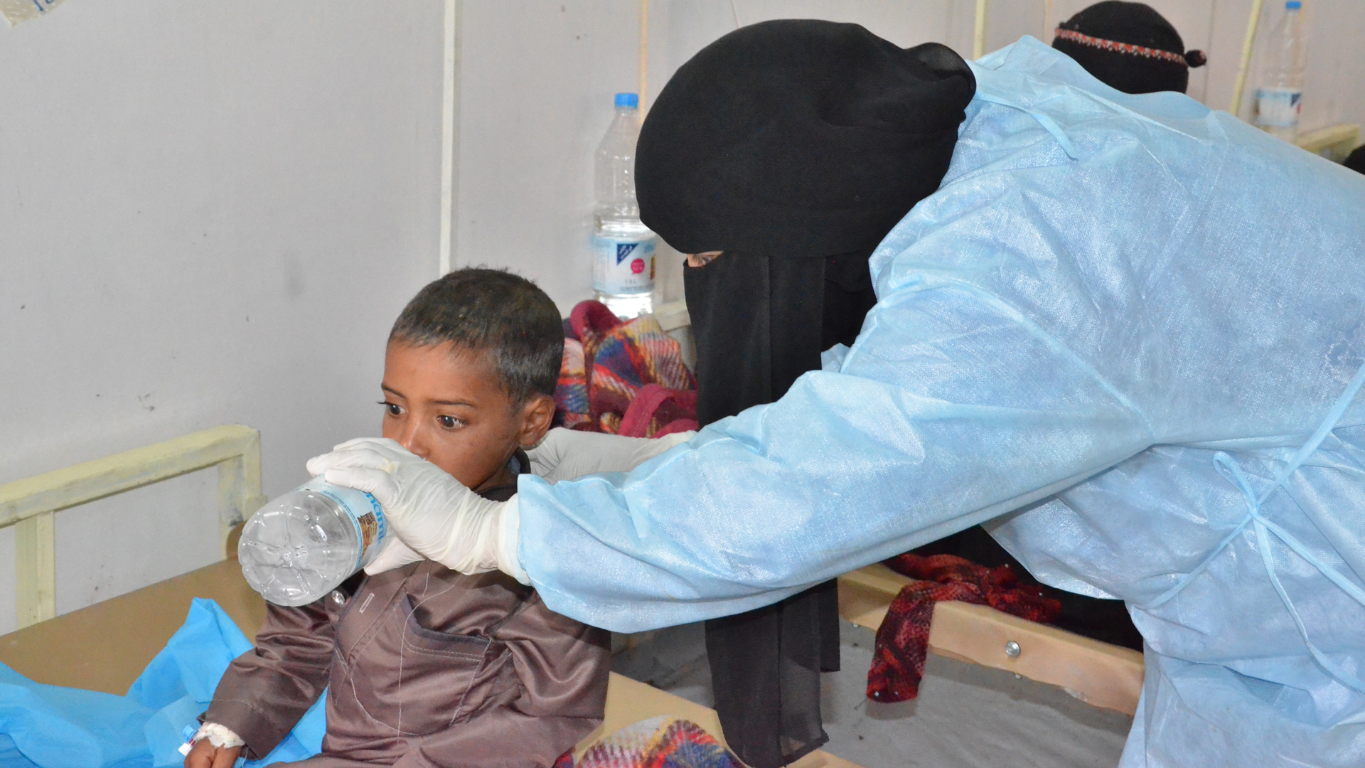 A MSF nurse helping a child drink water at MSF cholera treatment centre in Khamer.