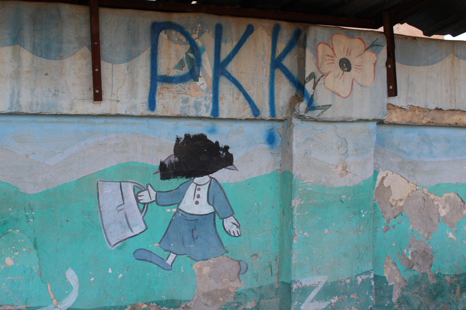 ISIS defaced the murals of this primary school in Sinjar city, PKK fighters tagged their affiliation on the wall after they helped take the town from the terror group.