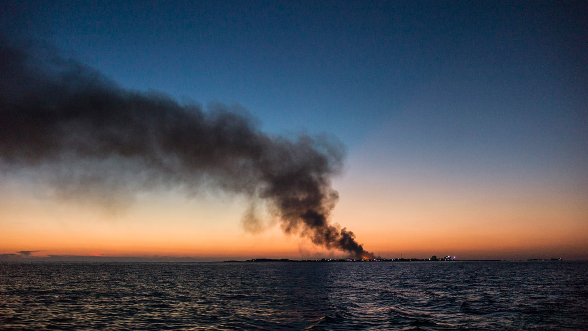 smoke billows on the horizon