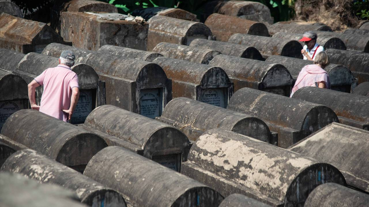 Besucher auf dem verwitterten jüdischen Friedhof in Yangon, Myanmar