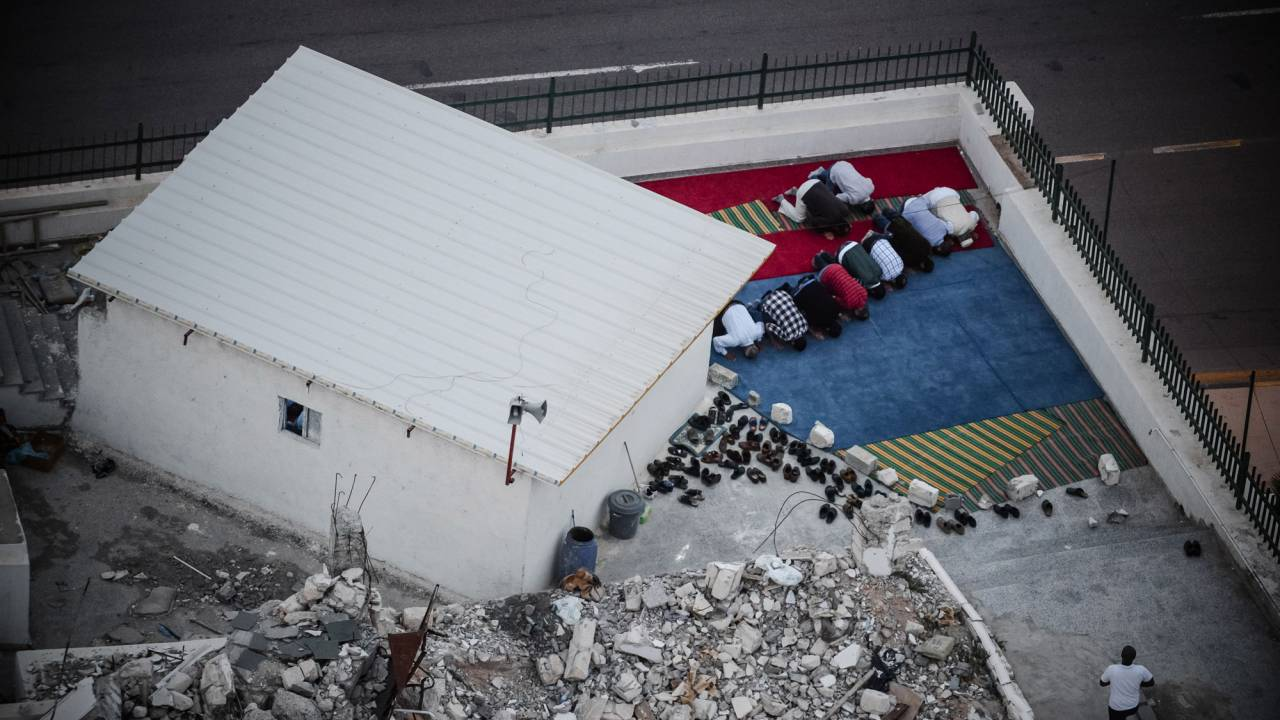 Men praying beside the ruins of their bombed mosque in Tripoli.