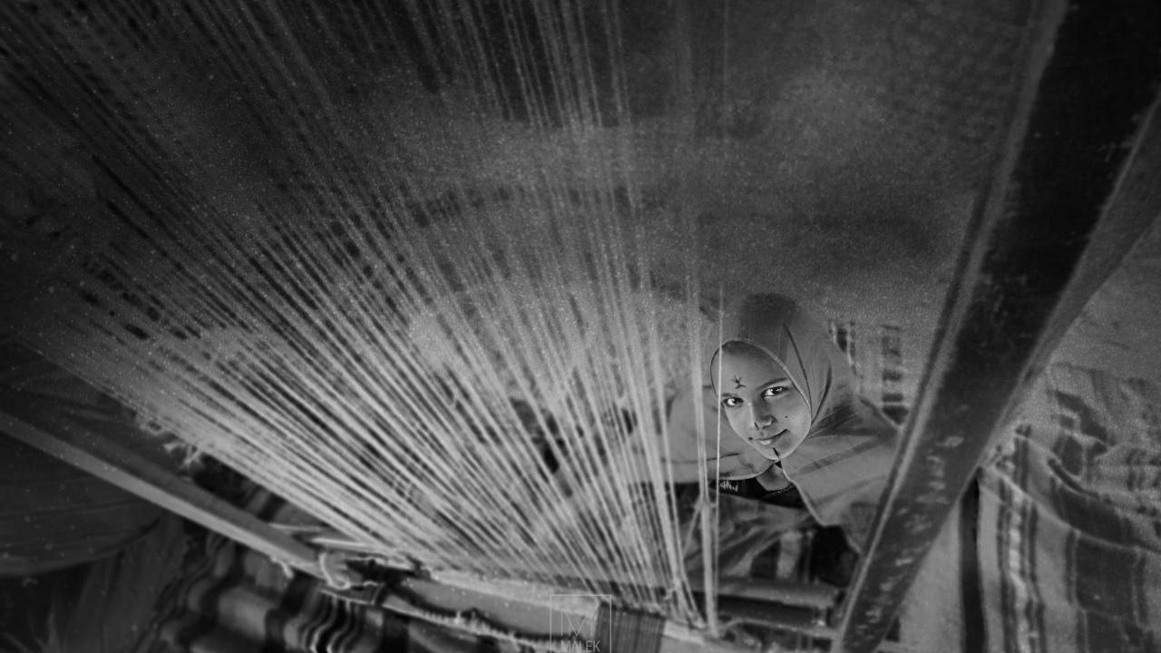Libysches Mädchen mit ihrem Webstuhl