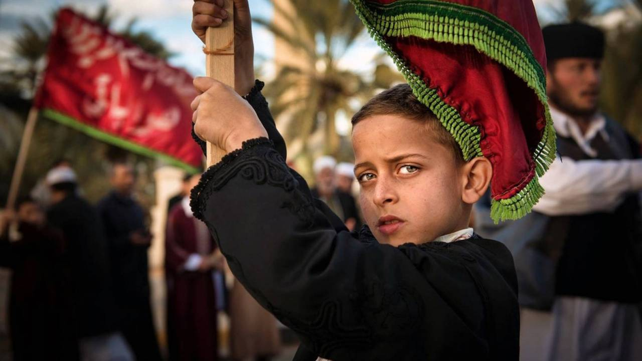 A boy with a flag at a parade.