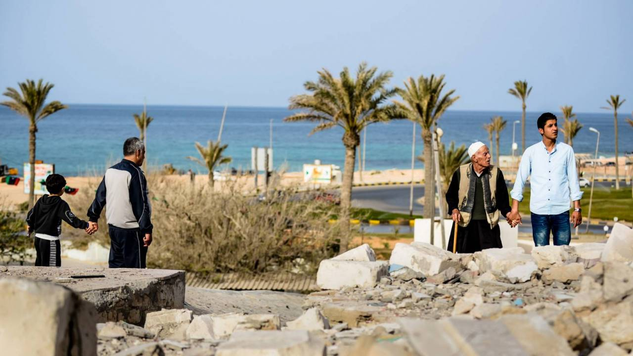 Families look at the bombed Al Andalusi shrine in 2013, a very significant icon of the city of Tajoura, in the east of Tripoli.