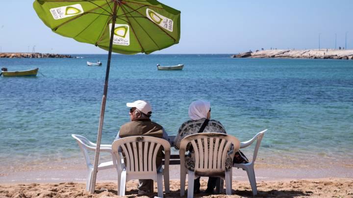 زوجين مسنين يسترخون على شاطئ جليم