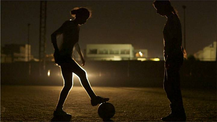فتيات يلعبن كرة القدم على اضواء السيارات