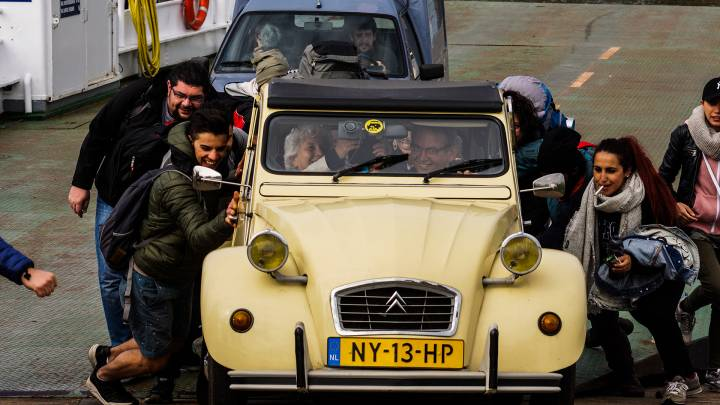 Keep pushing: Syrians help to get an old car started on a ferry across the river Meuse.