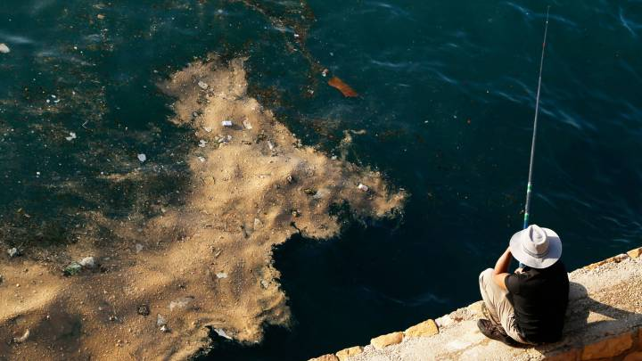 A fisherman in Beirut watches as dumped waste floats past his line.