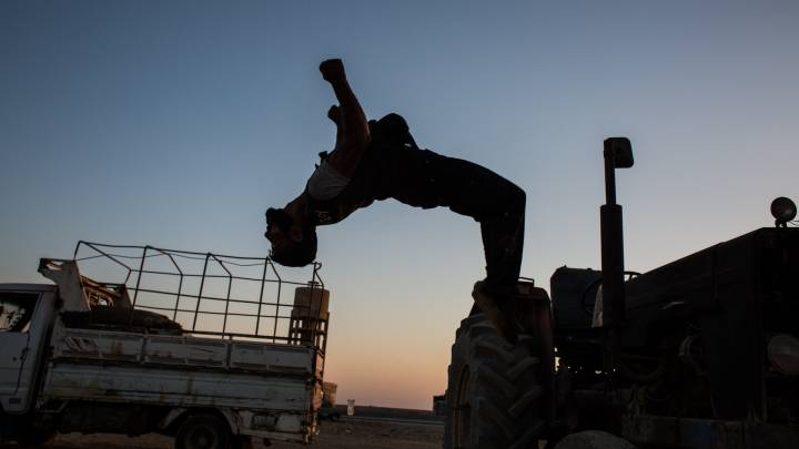A fighter of the YPG doing a backflip from a vehicle.
