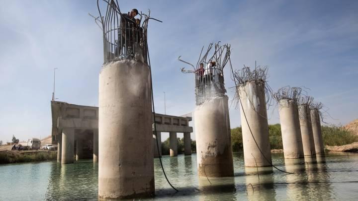 Men repair a bridge near Mosul, Iraq.