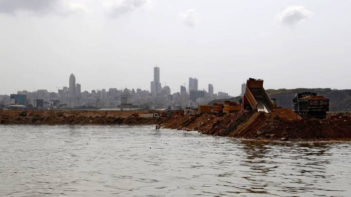 Trucks dump earth and trash into the sea as part of the land reclamation process at the Bourj Hammond landfill in Beirut.