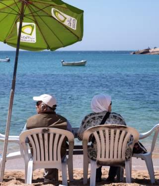 An elderly couple relax on Gleem Beach.