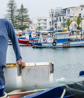 Jamel Mouhalib stands on his boat in the old port of Bizerte.
