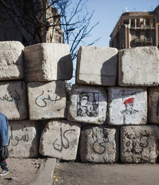 Youth clamber over a barrier in Cairo.